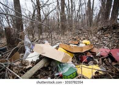 A pile of trash is left behind in the woods in the winter
