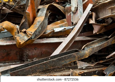 Pile of twisted and rusty scrap steel girders being recycled at a building demolition site.