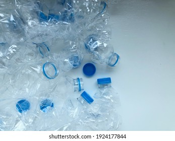 Pile of twisted transparent water bottle with blue cap are collected in recycle box. Bottle texture background with copy space for text.