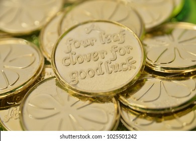 """A pile of two sided lucky gold coins with an Irish blessing that reads """"four leaf clover for good luck""""  one one side, with a four leaf clover on the other side, the pot of gold at the end of rainbow."""