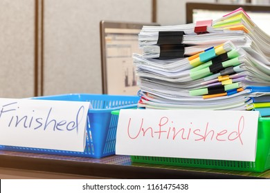 Pile of unfinished document on office desk. Stack of homework assignment archive with colorful paper and paper clip on teacher's table waiting to be managed and checked. Education and business concept