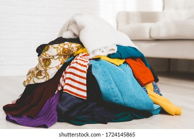 Pile of unfolded clothes for laundry on the floor. Heap of used clothes for donation and recycling. Concept of decluttering at home, minimalism, mess and wardrobe cleaning