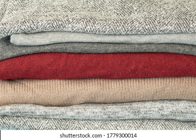 Pile of unisex clothes in grijs beige and burgundy color