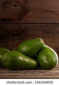 Pile of unpeeled bright green avocados on wood rustic table