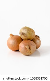 Pile of unpeeled and raw medium-sized yellow onions with golden skin on white background