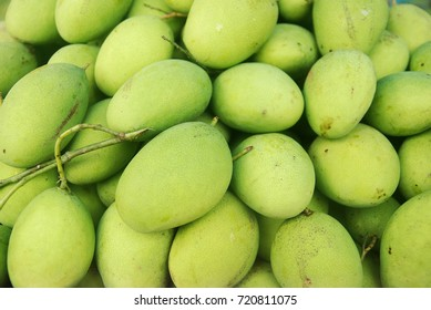 Pile of unripe mango on display for sale at open market.