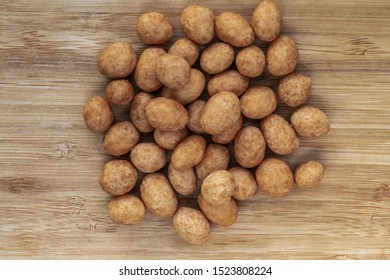 A pile of unshelled peanuts lies centrally on a brown wooden surface, top view, close-up