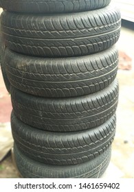 A pile of used black car tires at a puncture shop