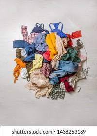 Haufen gebrauchter Kleidung auf hellem Hintergrund. Wiederverwertung