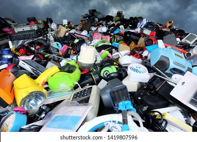 Pile of used Electronic and Housewares Waste Division broken or damage with sky and clouds are dark background, E-waste for Reuse and Recycle and is a problem with the environment concept.
