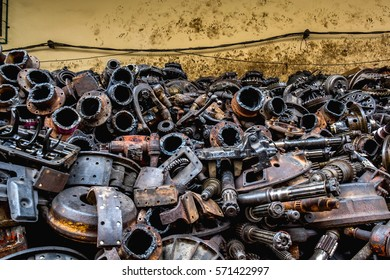 Pile of Used machine parts are oily and rusty in second hand machinery shop.