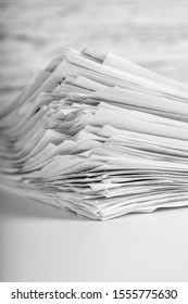 A pile of used paper sheets on a white table on a wooden table. Vertical view. The concept of financial reporting in business