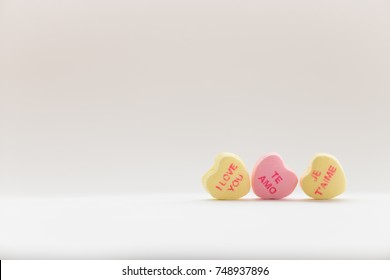 A pile of Valentine conversation candy hearts featuring the phrase I Love You in several languages