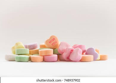 A pile of Valentine conversation candy hearts featuring the phrase Miss You