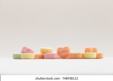 A pile of Valentine conversation candy hearts featuring the phrase #Love