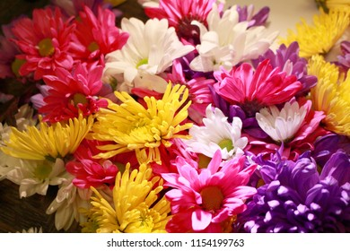 A pile of various flowers in pink, purple, yellow, and white