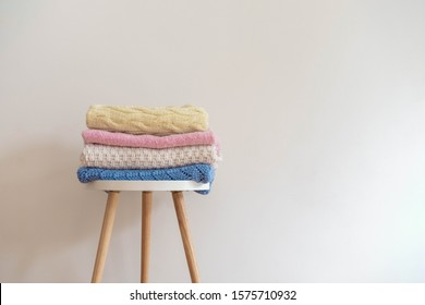 Pile of various woolen knitted blankets (sweaters) in pastel colors folded on a small round table on neutral background. Warm and cozy home mood concept. Image with copy space