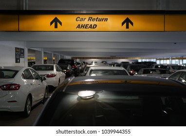 pile of vehicles in an airport rental car return area including a sign of car return ahead, which reminds insurance is important for no regrets
