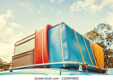 Pile of vintage bags on roof of the travel car fastened with rope