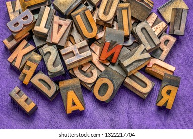 pile of vintage letterpress wood type printing blocks against violet bark paper