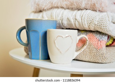 A pile of warm knitted sweaters on the table. Warm winter knitted clothes on the table. A cups of coffee or tea and pullovers, winter fashion concept