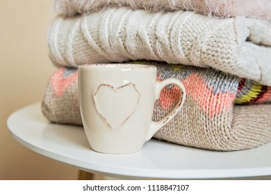 A pile of warm knitted sweaters on the table. Warm winter knitted clothes on the table. A cup of coffee or tea and pullovers, winter fashion concept