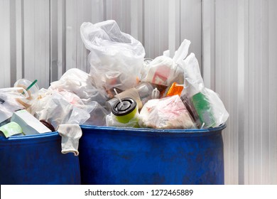 Pile of waste on the blue bins, Plastic Bin blue color for recycle garbage waste outdoors front Zinc wall, Plastic Bin of Garbage, Bin Trash of Waste Plastic Pollution, Dirty Bin for waste garbage