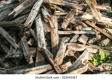 Pile of weathered firewood stacked randomly as background