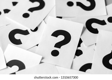 Pile of white cards with black question marks in close-up, full frame vertical background concept
