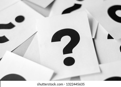 Pile of white cards with black question marks viewed in full frame close-up background concept