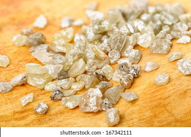 A pile of white grey uncut and rough diamonds on birch wood