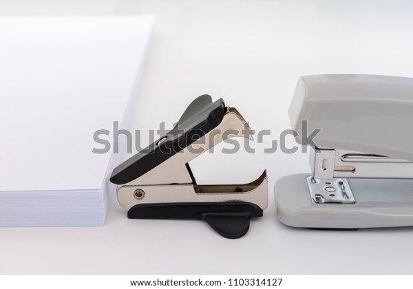 pile of white office paper, black staple remover and gray stapler on white background, concept abstract background