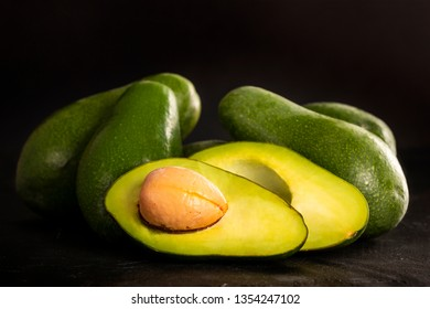Pile of whole and cut ripe avocados placed on shabby timber tabletop