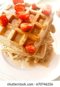 A pile of whole wheat waffles with strawberries and maple syrup. Selective focus.