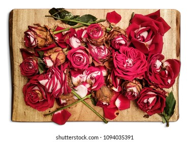 Pile of withered red roses is placed on a wooden board - an artistic decadence look