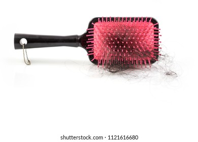 Pile of women's hair loss problem, hairs fall with pink brush on white background.