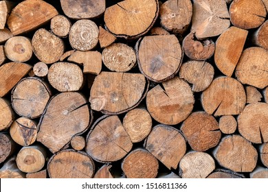 Pile of wooden logs stacked together on top of each other. Wall of stacked wood logs as background. stack of logs. Stack of firewood close up. Logs cuts prepared for fireplace.