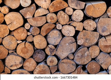 Pile of wooden logs stacked together on top of each other. Wall of stacked wood logs as background. stack of logs. Stack of firewood close up. Logs cuts prepared for fireplace. selective focus