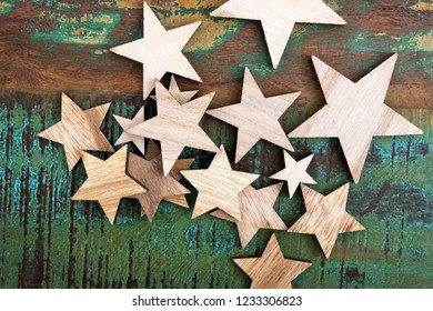 A pile of wooden stars lie on a colored wooden table