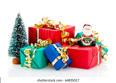 Pile of wrapped Christmas presents with tree and Santa Claus figurine, isolated on white background.