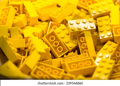 Pile of yellow color building blocks with selective focus and highlight on one particular block using available light.