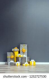 A pile of yellow and grey Christmas gifts with ribbons against the wall on a beautiful hardwood floor with copyspace