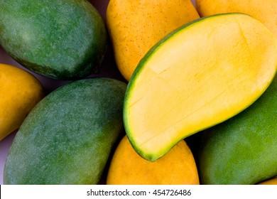 a pile yellow ripe mango and fresh green mango and half mango  on white background healthy fruit food isolated