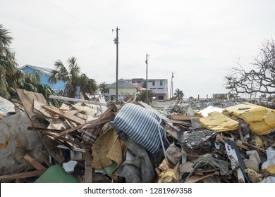 Piled debris with destroyed houses in the back ground in the aftermath of hurricane Michael in Mexico Beach Florida