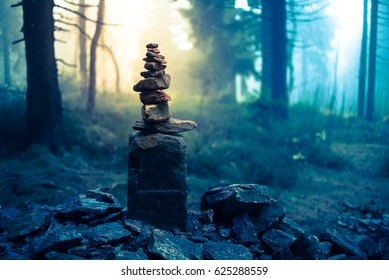 Piled good luck stones showing the way for lost ones in enchanted forest. Beautiful mysterious woods landscape background in Czech Orlicke Hory mountains - Magical fog light Happy Halloween card
