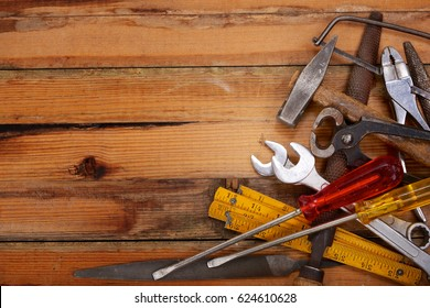 Piled hand tools on a wooden workbench