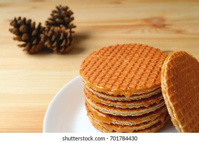 Piled up Stroopwafel on White Plate Served on Wooden Table with Blurred Pine Cones in the Background