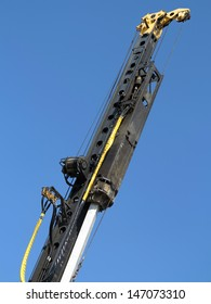 Pile-driver in action against the blue sky.