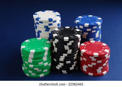 Piles of casino chips on dark blue table cloth