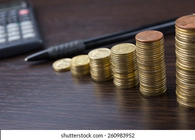 Piles of coins with calculator and pen on a wooden background. Business composition. Business concept. Financial close-up background.